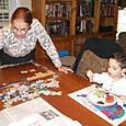 Nanny working on a ridiculous puzzle while Josh snacks